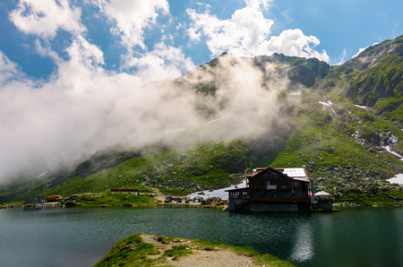 lake Balea of Fagaras mountains. lovely summer landscape with low clouds around the peak Editorial