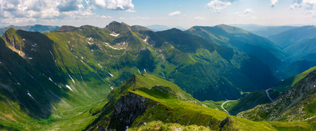 panorama of Fagarasan mountain ridge in summertime. lovely landscape with cliffs and grassy hills over the valley. TransFagarasan road in the left corner runs through the valley in to the distance