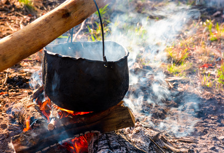 cauldron in steam and smoke on open fire. outdoor cooking concept. old fashioned way to make food Banque d'images
