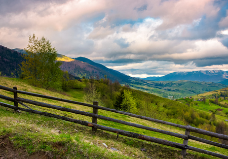 wooden fence across the hill. beautiful agriculture scenery of Carpathian mountains on a cloudy springtime day Stock Photo