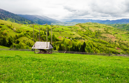 woodshed on grassy hill in rural area. beautiful springtime countryside landscape.