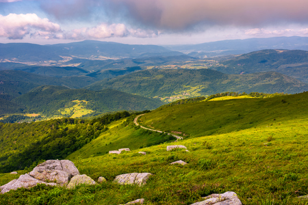 lovely landscape on Runa mountain. summer scenery on a cloudy day in beautiful light. huge rocks on a grassy meadow Stock Photo