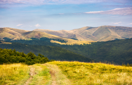 country road through grassy hillside. lovely summer scenery of Carpathian mountains. Svydovets mountain ridge in the distance