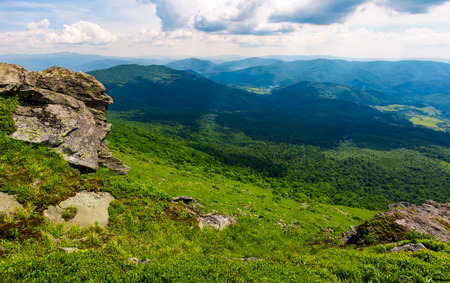 rocky cliff over the grassy valley. beautiful summer landscape with mountain ridge in the distance Stock Photo