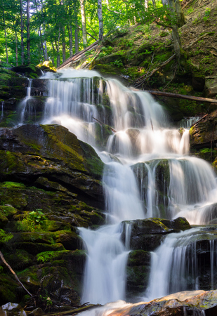 cascades of big waterfall in forest. beautiful summer scenery at sunrise. beams of light on water splashes. nature power and beauty concept 스톡 콘텐츠