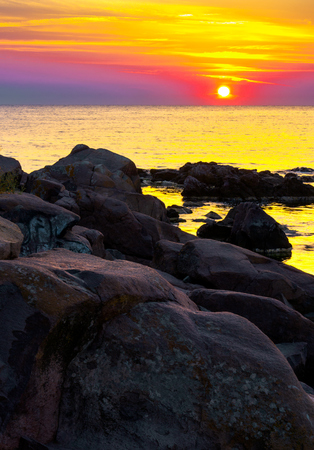 reddish sunrise over the sea with rocky shore. beautiful summer scenery and vacation concept