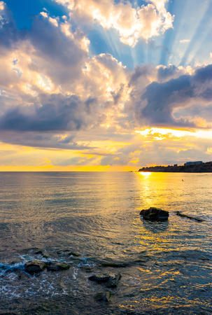 gorgeous sunrise at the seaside. sunbeams come from behind the cloud. sun reflects on rippled water surface. calm wave touch rocky shore. beautiful summer scenery and vacation concept Banco de Imagens