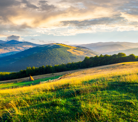 beautiful rural scenery in mountains at sunrise. haystack on the field behind the fence. outdated agriculture approach concept Stock Photo