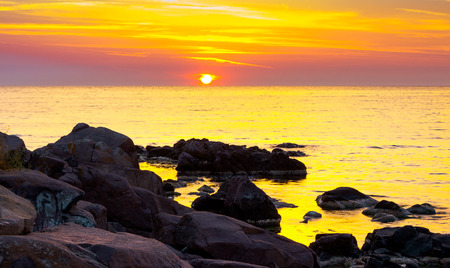 reddish sunrise over the sea with rocky shore. beautiful summer scenery and vacation concept Imagens - 101072808