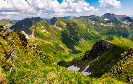 valley with snow in summer mountains. gorgeous mountainous landscape of Carpathians. rocky cliffs and grassy hillsides under a cloudy sky. Fagaras ridge of Southern Carpathian mountains, Romania Stock Photo