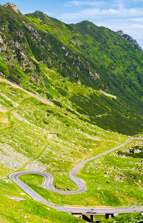 Legendary Transfagarasan road in Romanian mountains. winding serpentine among the grassy hills on a sunny morning Stock Photo