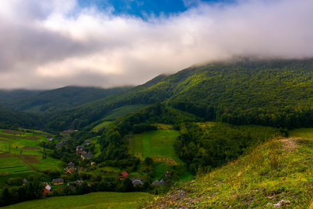 small Carpathian village in mountains. beautiful landscape with forested hills and agricultural fields on a cloudy morning Stock Photo