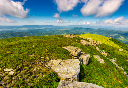 mountainous landscape in summer. lovely scenery with rocky formation on the grassy hill under the blue sky with some clouds.