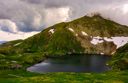 glacier lake Capra at the foot of the mountain. lovely summer scenery on a cloudy day. popular travel destination in Southern Carpathian mountains of Romania Stock Photo - 101904126