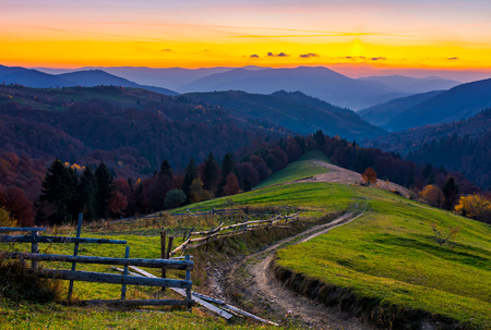 country road winding down the hill at dusk. forested mountain ridge in the distance. lovely scenery of Synevyr National park area, Ukraine Banco de Imagens - 101904164