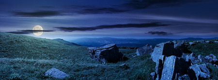 beautiful panorama of Runa mountain at night in full moon light. huge rocky formation on the hillside and peak in the distance. wonderful landscape of Carpathians
