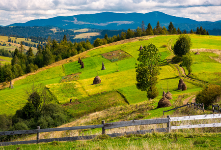 fence in front of a rural fields on hills. haystack on a grassy slope and mountain ridge in the distance