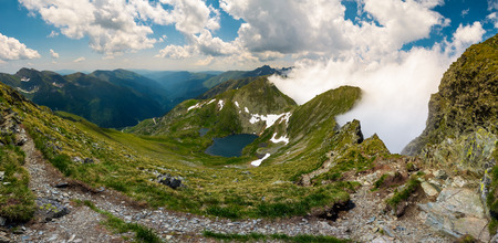 Gorgeous landscape of Fagaras mountains in summer. clouds rising above the rocky cliffs. lake Capra down the grassy slope in the valley. view from the tourist path on top of the ridge.
