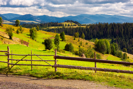 fence in front of a rural fields on hills. haystack on a grassy slope and mountain ridge in the distance Stock Photo - 102851779