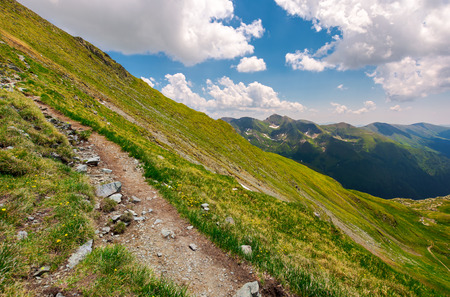 tourist path through grassy slope of Fagaras mount. beautiful summer landscape under the cloudy sky Stock Photo