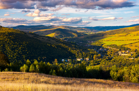 beautiful Carpathian countryside at sunset. village down in the valley in shade of a nearby mountain. beautiful colorful sky with clouds. Great water dividing ridge in the far distance