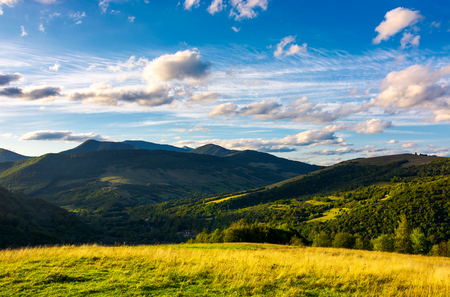 beautiful mountain landscape in afternoon. grassy meadow and forested hills of Carpathian mountains. Pikui mountain in the far distance. gorgeous blue sky with golden clouds Stock Photo