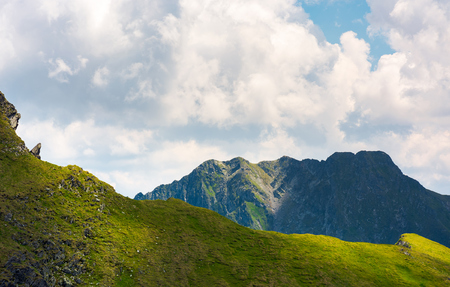 rocky ridge behind the grassy hill under the cloud. lovely mountainous scenery in summer Stock Photo