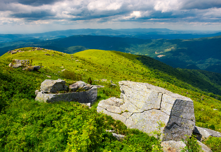boulders on grassy hills. beautiful mountainous landscape. distant mountain under the cloudy sky. view in to the valley from the top of Runa mountain Stock Photo