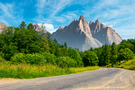 road through forest in to the mountains. composite mountainous landscape with rocky peaks in the distance. beautiful summer nature with gorgeous sky. travel and explore unknown places concept