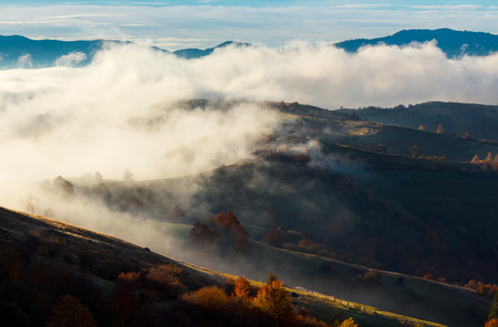 cloud inversion in autumn mountains. beautiful nature scenery. fog rolling above the rural fields in forenoon Stock Photo