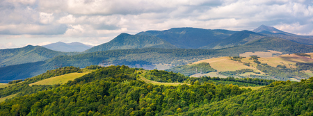 panorama of beautiful Carpathian countryside. power lines run across the nearest hill. Pikui and Gosrta mountains are seen in the distance under the cloudy sky Stock Photo
