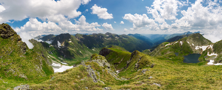 panorama of Fagaras mountain ridge in summer. beautiful view in to the valley of beautiful landscape with gorgeous cloudscape. rocky cliffs above the grassy slopes with some snow. Stock Photo