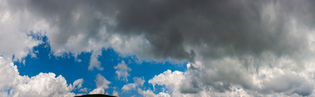 amazing cloud formations on a dark blue sky. beautiful side lit cloudscape panorama in summer Stock Photo - 103702345