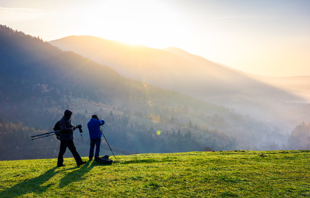 photographers on workshop at sunrise. capturing gorgeous scenery of mountainous area from the top of grassy hill. beautiful landscape with sun rising behind the forested mountain and foggy valley Stock Photo - 103702378