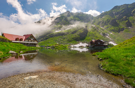 rising clouds on lake Balea. beautiful summer landscape of popular tourist attraction. one of the most visited locations near the Tranfagarasan road Stock Photo - 104189338