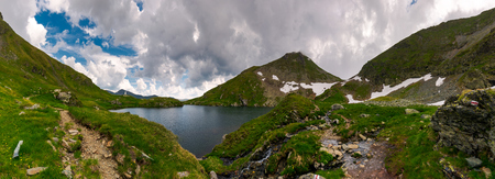 panorama of Capra lake, Romania. gorgeous landscape of Fagarasan mountains on a cloudy summer day 스톡 콘텐츠