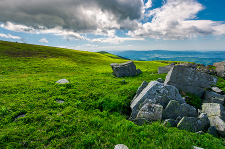 boulders on a grassy slopes of Runa mountain. lovely mountainous landscape on a cloudy summer day