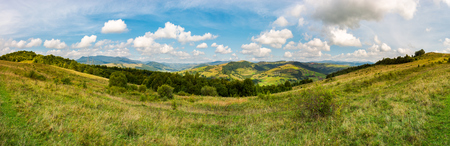 panorama of mountainous TransCarpathia countryside. beautiful autumnal landscape. gorgeous cloudscape on a blue sky. forest on the grassy hill. Pikui mountain in the distance