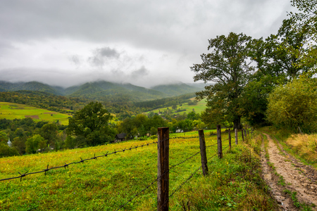 road along the fence in rural outskirts. pasture behind the barbwire. mountainous countryside on a dull day with overcast sky. village down in the valley. some old oak trees along the path