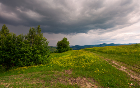 path across the grassy hill. lovely summer scenery. hiking and outdoor activities concept. dark cloudy sky. Stock Photo - 104417810