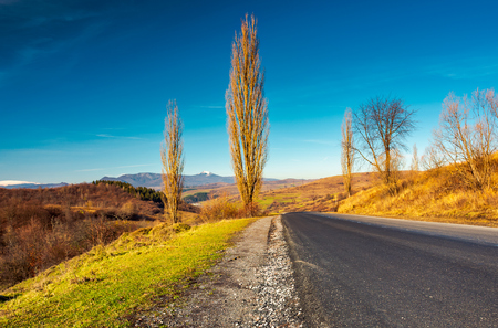 new asphalt road in to the mountains. Pikui mountain with snowy top in the distance. beautiful sunny weather in late autumn. location Volovets serpentine, TransCarpathia, Ukraine Stock Photo - 104417818