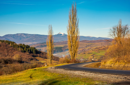 new asphalt road in to the mountains. Pikui mountain with snowy top in the distance. beautiful sunny weather in late autumn. location Volovets serpentine, TransCarpathia, Ukraine Stock Photo - 104417821