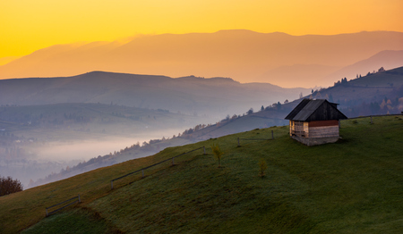 woodshed on a hillside at sunrise. beautiful countryside scenery of mountainous area. yellow sky over the purple mountains. fog down the valley of Synevir village, TransCarpathia, Ukraine Stockfoto