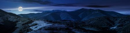 beautiful panorama of mountain ridge at night in full moon light. wonderful landscape in early autumn 写真素材