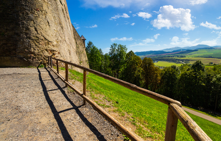 Castle wall and railing on a hill. view in to the beautiful mountainous landscape