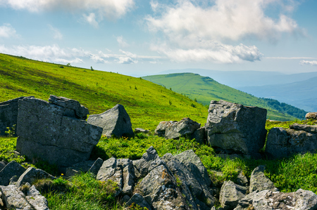 Huge rocky formations on the grassy hills. beautiful mountain landscape in late summer on a cloudy day. location Runa mountain, Ukraine