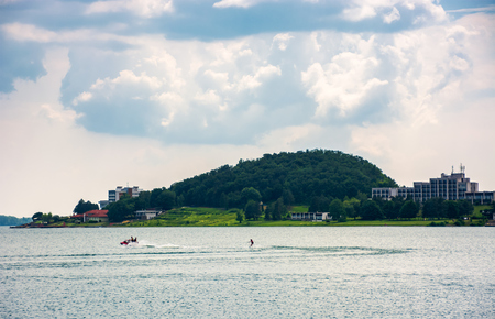 Medvedia mountain over the Zemplinska Sirava lake, Slovakia. Lovely place for vacation or weekend in summer. people water skiing on one of the largest Slovakian body of water