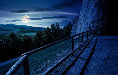 castle wall and railing on a hill at night in full moon light. view in to the beautiful mountainous landscape