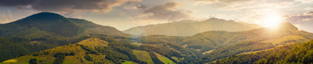 panorama of beautiful mountain ridge at sunset in evening light. perfect countryside landscape. rural field on the nearest forested hills. Mighty Borzhava ridge in the distance Stock Photo