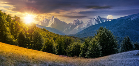 day and night composite of mountainous landscape. time change concept. perfect countryside scenery with beech forest on a grassy hillside and High Tatra mountain ridge in the distance Stock Photo